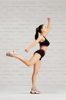 Jeune femme sportive a écarté ses bras sur les côtés, a soulevé sa jambe
