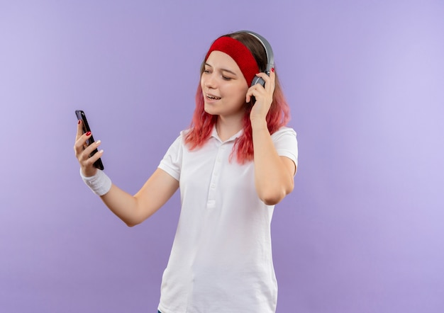Jeune femme sportive écoute de la musique avec ses écouteurs en regardant l'écran de son smartphone souriant debout sur le mur violet