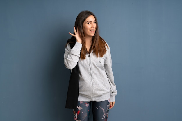 Jeune femme sportive écoute quelque chose en mettant la main sur l'oreille