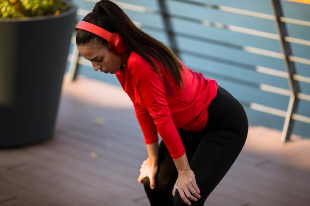 Jeune femme sportive avec des écouteurs prenant la pause après une course en milieu urbain