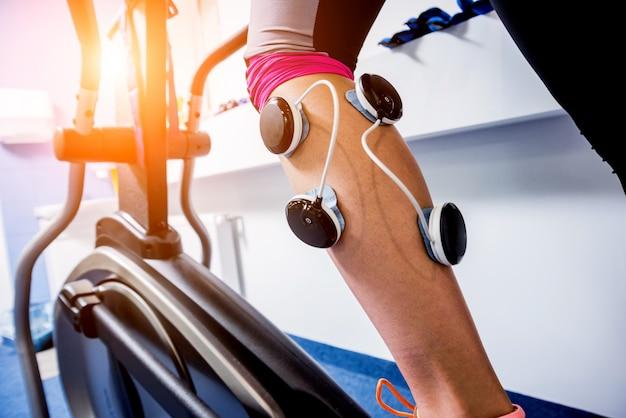 Jeune femme sportive avec électrostimulateur sur les muscles des jambes.