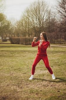 Une jeune femme sportive est engagée dans des exercices sportifs dans un parc au printemps, en plein air. femme professionnelle en costume rouge lors d'une session de formation. concept de mode de vie sain. espace de copie pour le site