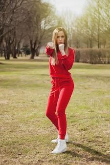 Une jeune femme sportive est engagée dans des exercices sportifs dans un parc au printemps, en plein air