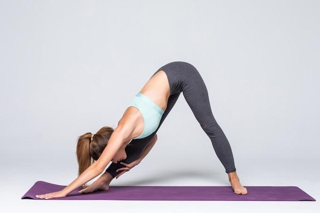 Jeune femme sportive étend le dos assis sur les genoux et tenant ses mains droites sur le sol isolé