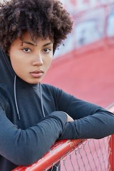 Jeune femme sportive a une expression réfléchie, porte un sweat-shirt décontracté avec capuche