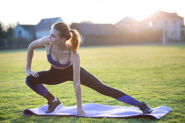 Jeune femme sportive, faire de l'exercice avant de courir dans le champ du matin à l'extérieur.