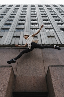 Jeune femme sportive faisant du parkour en ville. la fille engagée dans le freerunning.