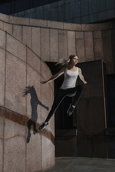 Jeune femme sportive faisant du parkour en ville