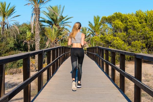 Jeune femme sportive faisant de l'exercice et courant dans le parc