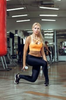 Jeune femme sportive faisant des exercices avec des haltères en salle de sport