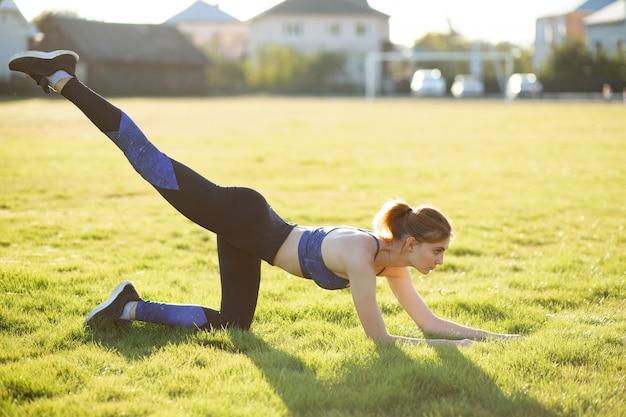 Jeune femme sportive faisant des exercices de remise en forme sur l'herbe verte en chaude journée d'été à l'extérieur.