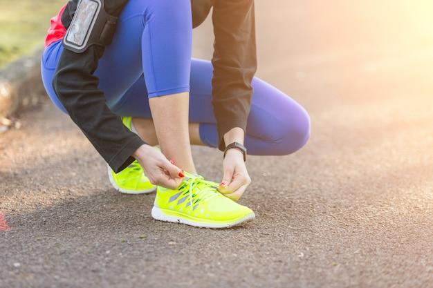 Jeune femme sportive fait ses chaussures avant de courir.