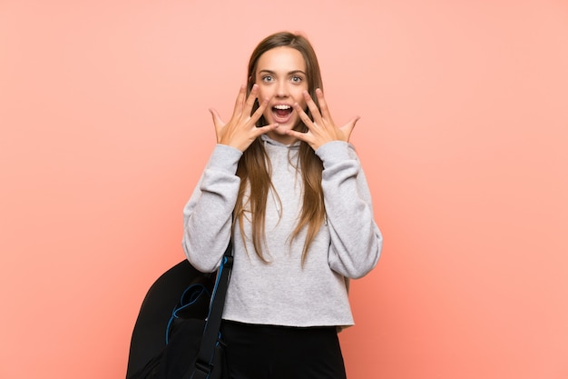 Jeune femme sportive sur fond rose isolé avec une expression faciale surprise