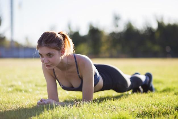 Jeune femme sportive en formation de vêtements de sport dans le champ au lever du soleil. jeune fille debout en position de planche sur l'herbe dans un parc de la ville.
