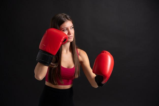 Jeune femme sportive avec des gants de boxe sur fond noir isolé
