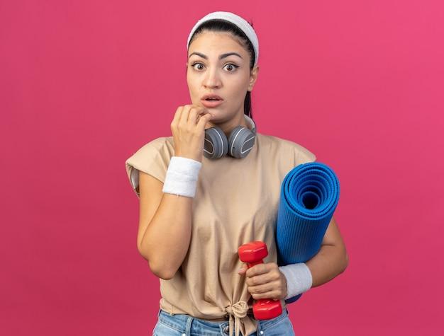 Jeune femme sportive impressionnée portant un bandeau et des bracelets avec des écouteurs autour du cou regardant devant tenant un haltère et un tapis de fitness touchant le menton isolé sur un mur rose
