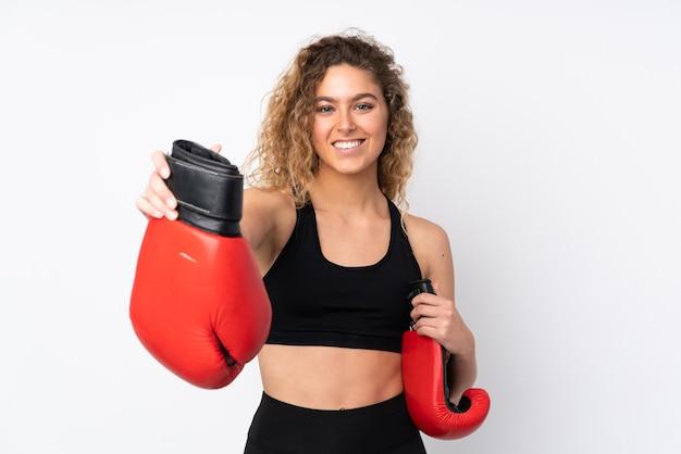 Jeune femme sportive isolée sur blanc avec des gants de boxe