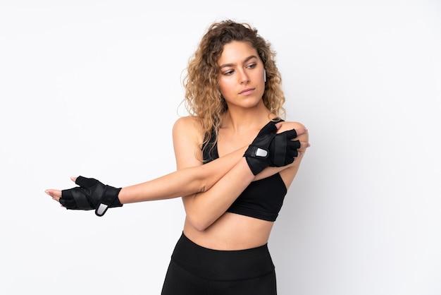 Jeune femme sportive isolée sur le bras d'étirement de mur blanc