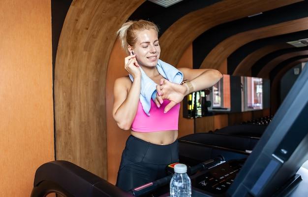 Jeune femme sportive joyeuse avec une serviette sur les épaules sur un tapis roulant regarde une montre intelligente
