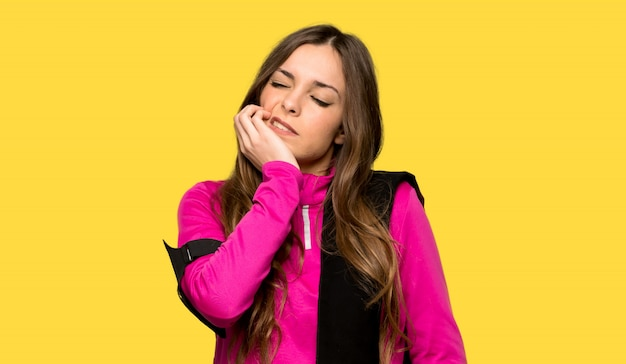 Jeune femme sportive avec maux de dents sur fond jaune isolé