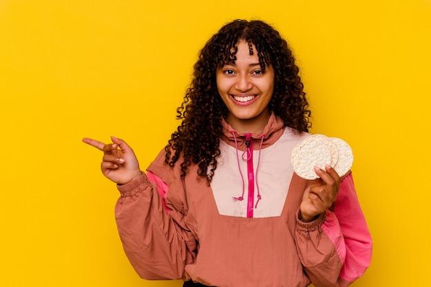 Jeune femme sportive métisse tenant un gâteau de riz isolé sur fond jaune souriant et pointant de côté, montrant quelque chose dans un espace vide.