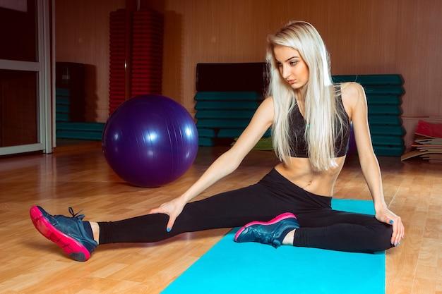 Jeune femme sportive mince dans la salle de gym faire ses exercices et assis sur le karemat