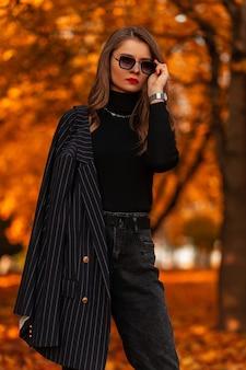 Jeune femme sportive mince faisant du jogging dans des vêtements de sport bleus à la mode en chaussures de sport dans un parc public contre un coucher de soleil lumineux. fille sportive blonde avec un corps magnifique avec un cul sexy qui traverse la forêt. vue arrière.