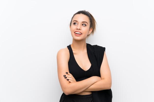 Jeune femme sportive sur un mur blanc, levant en souriant