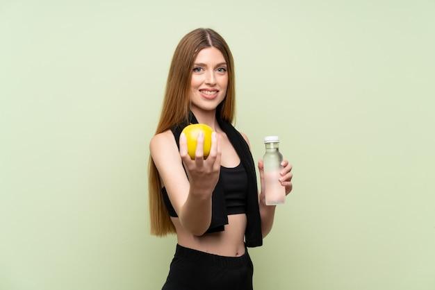 Jeune femme sportive sur un mur vert isolé avec une pomme