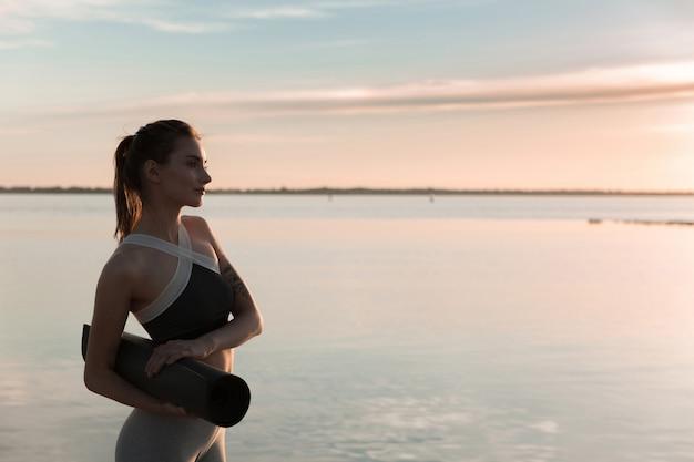 Jeune femme sportive à la plage debout avec tapis