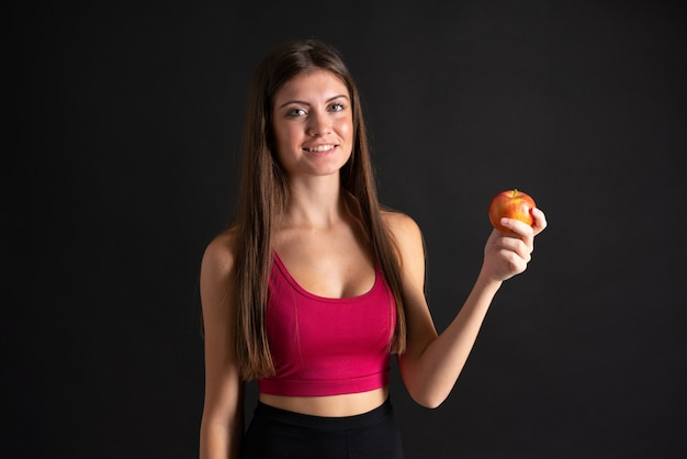 Jeune femme sportive avec une pomme sur un mur noir isolé