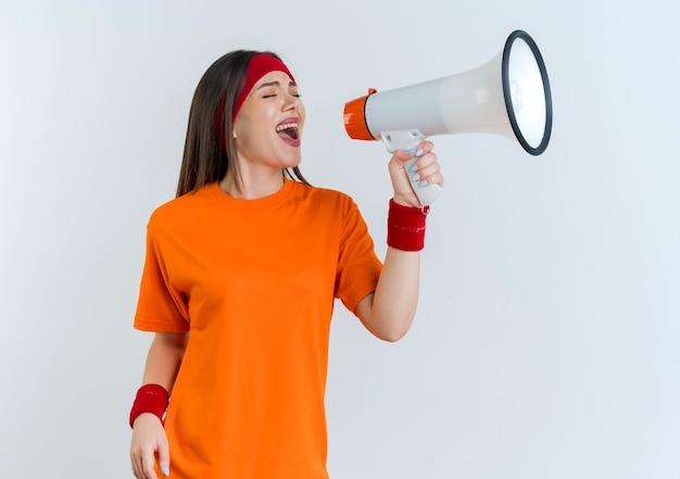 Jeune femme sportive portant un bandeau et des bracelets tournant la tête à l'autre en criant dans le haut-parleur avec les yeux fermés isolés