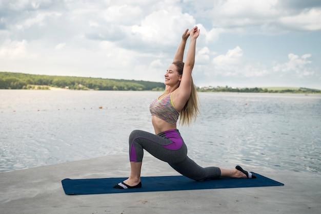 Jeune femme sportive pratiquant la gymnastique asana et étirement des muscles sur un tapis de yoga au bord du lac le matin
