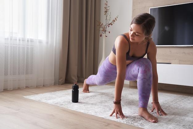 Jeune femme sportive pratiquant le yoga à la maison dans le concept de sport et de remise en forme de salon