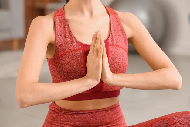 Jeune femme sportive pratiquant le yoga à la maison