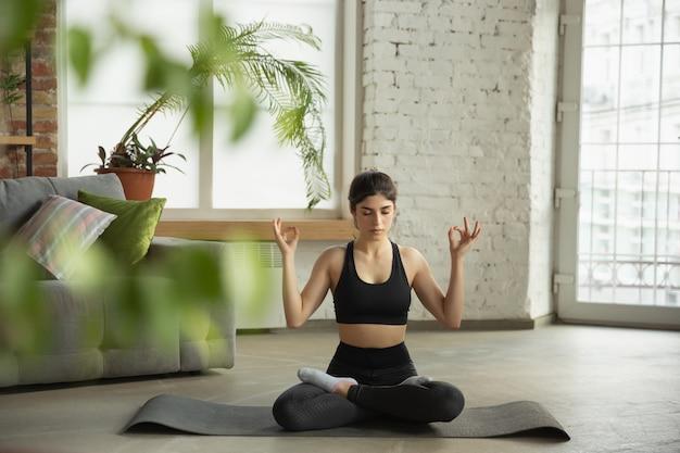 Jeune femme sportive prenant des cours de yoga en ligne et pratique à la maison