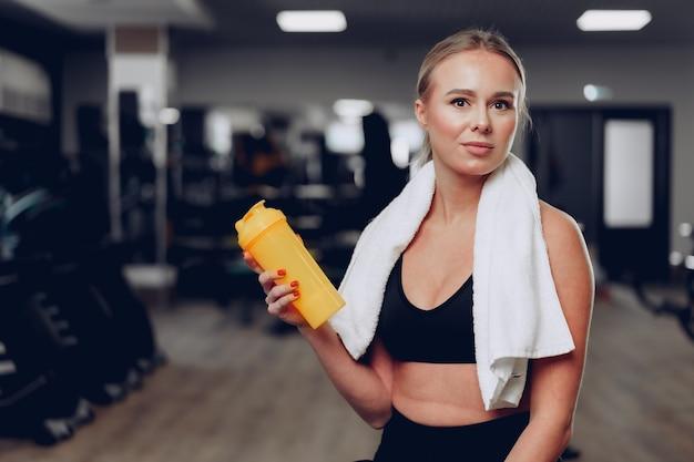 Jeune femme sportive prenant un verre dans une salle de sport après l'entraînement