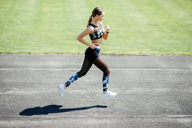 Jeune femme sportive qui court dans un stade d'athlétisme