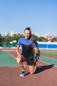 Jeune femme sportive qui s'étend au stade