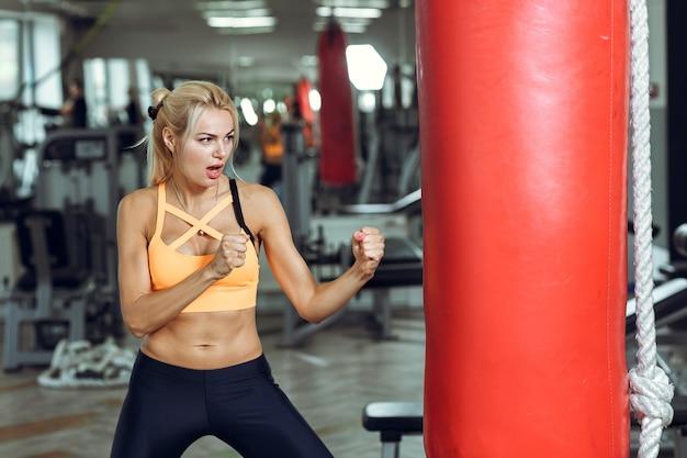 Jeune femme sportive s'entraînant avec un sac de boxe au gymnase
