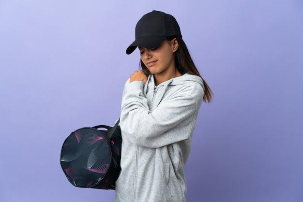 Jeune femme sportive avec sac de sport souffrant de douleurs à l'épaule pour avoir fait un effort