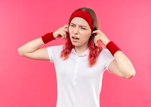 Jeune femme sportive en serre-tête fermant les oreilles avec les doigts avec une expression agacée debout sur un mur rose