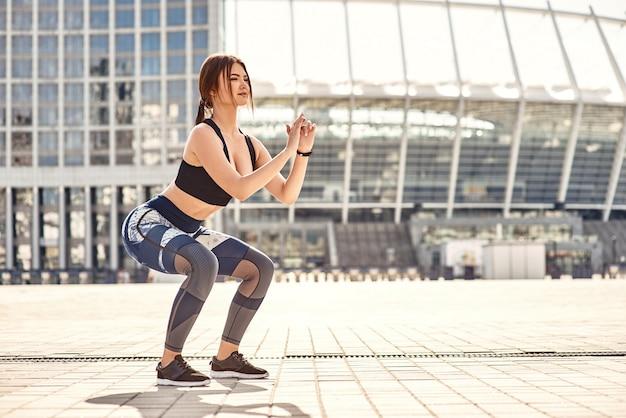 Jeune femme sportive squat parfaite en vêtements de sport faisant des squats tout en faisant de l'exercice à l'extérieur dans le