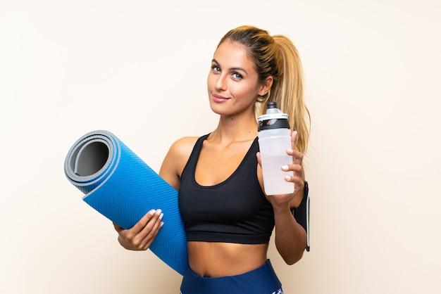 Jeune femme sportive avec tapis sur mur isolé