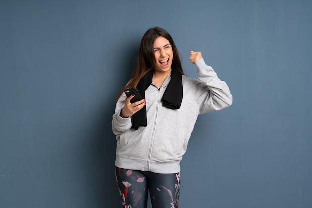 Jeune femme sportive avec téléphone en position de victoire