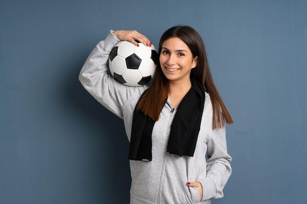 Jeune femme sportive tenant un ballon de foot