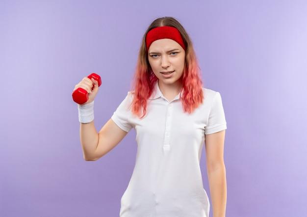 Jeune femme sportive tenant des haltères à la main avec un visage sérieux debout sur un mur violet