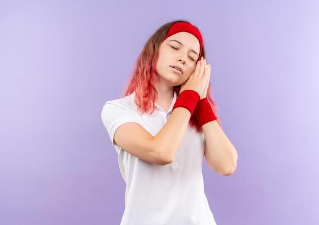 Jeune femme sportive tenant les paumes ensemble se penchant la tête sur les paumes à la fatigue veut dormir debout sur le mur violet