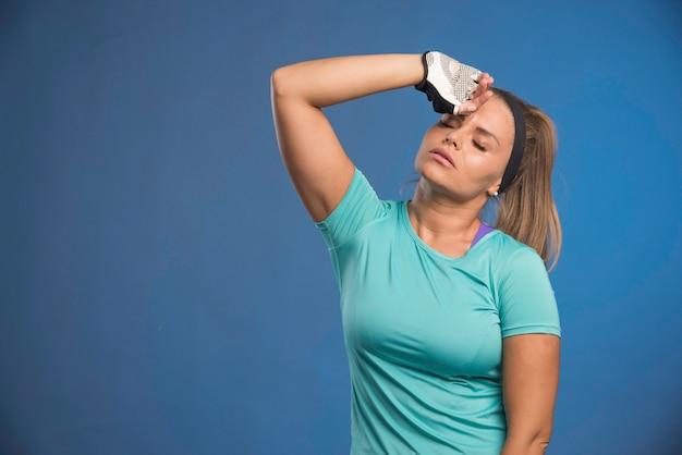 Jeune femme sportive tenant son front.