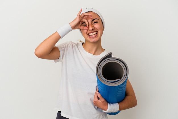 Jeune femme sportive tenant un tapis isolé sur un mur blanc excité en gardant le geste ok sur les yeux.